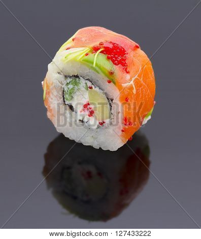 Japanese Cuisine. Sushi Roll With Salmon Avocado And Tobiko Over Black Background.