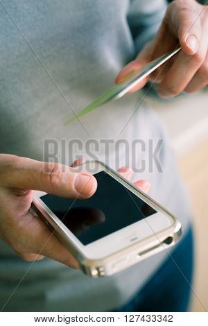 Woman with credit card ant mobile phone in the hand