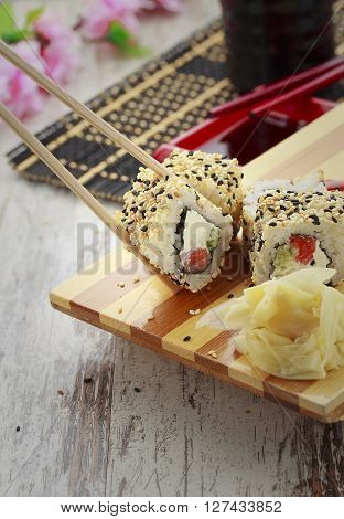 Japanese Cuisine. Sushi Set And One Peace Of Roll In Chopsticks.