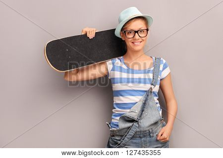 Hipster girl holding a skateboard and leaning against a wall