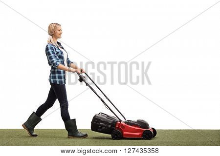 Profile shot of a young cheerful woman mowing a lawn with a lawnmower isolated on white background