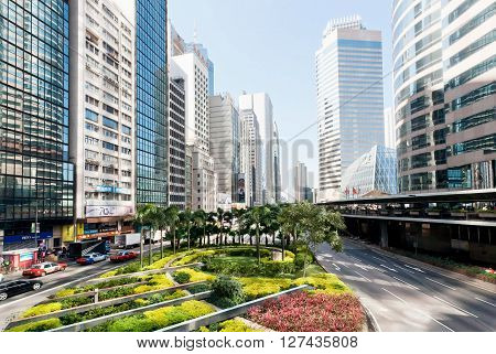 HONG KONG, CHINA - FEBRUARY 7, 2016: Urban scene with huge scyscrapers of glass and concrete and small grenn area of city on February 7, 2016. More than 47 million tourists visit Hong Kong annually