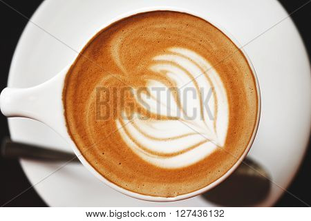 Cappuccino with beautiful foam and spoon in white cup. Latte art, top view.