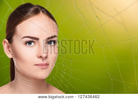 Young female and clean fresh skin. The reinforcement with threads. The beautiful woman face  with arrows close up over green background with web