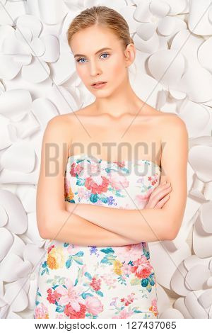Beautiful tender woman with blonde hair posing by a background of white paper flowers. Beauty, fashion. Spring, summer concept.