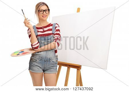 Young blond woman holding a paintbrush in front of a blank canvas isolated on white background