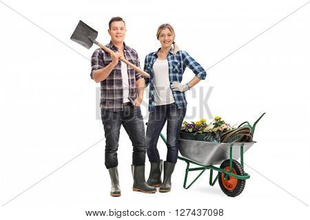 Full length portrait of a woman holding a rake and posing next to a wheelbarrow full of gardening equipment and flowers isolated on white background
