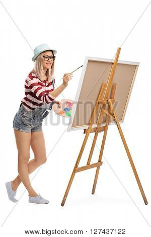Full length portrait of a young woman painting on a canvas with a paintbrush isolated on white background