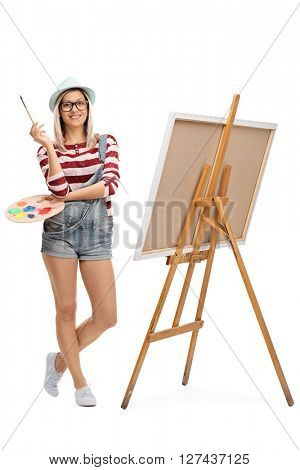 Full length portrait of a young woman posing with a paintbrush by an easel isolated on white background