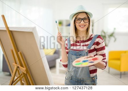 Cheerful female painter posing at home and holding a paintbrush and a color palette