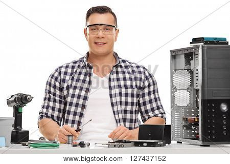 Cheerful PC technician sitting at a table and repairing a computer isolated on white background