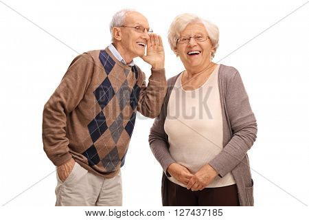 Studio shot of an old man whispering something to his wife isolated on white background