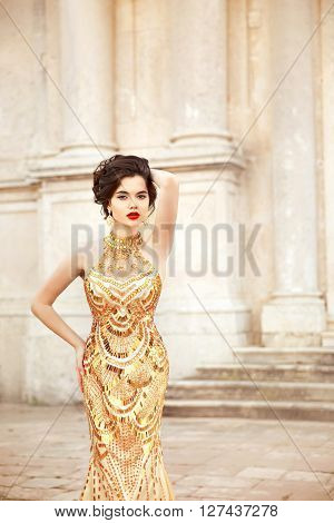 Fashion Model In Gold Dress. Beautiful Sexy Brunette In Elegant Luxury Gown. Girl With Red Lips Make