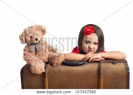 Capricious beautiful little Girl with suitcase and toy bear