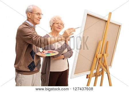 Elderly couple painting on a canvas together with paintbrushes isolated on white background