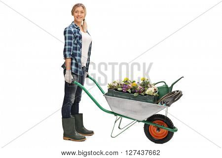 Full length portrait of a female gardener pushing a wheelbarrow full of gardening equipment isolated on white background