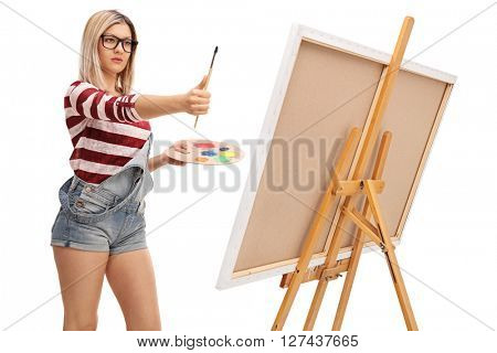 Blond female artist measuring proportions on a painting with a paintbrush isolated on white background