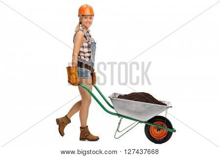 Female construction worker pushing a wheelbarrow full of dirt and looking at the camera isolated on white background