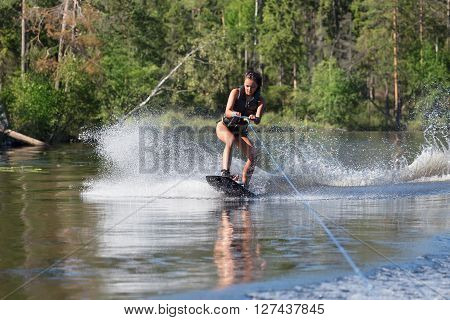 Young woman study riding wakeboarding on a lake