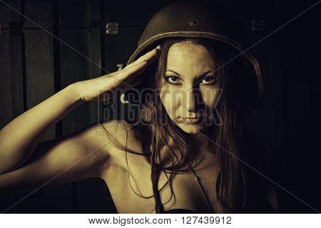 Pretty woman in helmet making salute gesture in a storage