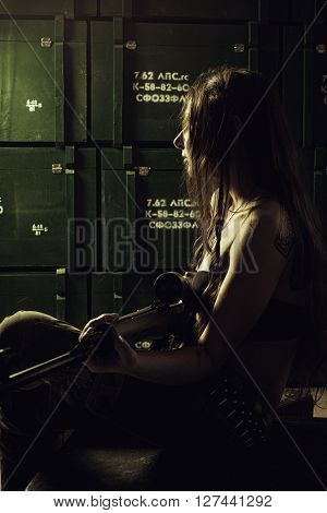 Pretty girl with sniper rifle sitting in a storage