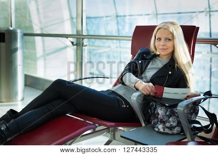 Young Pretty Blonde Woman With Air Travel Tickets Sitting In Arport