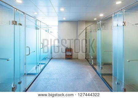 glass showers in modern washing room in gym