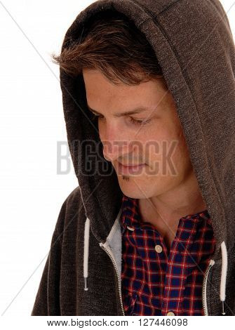 A handsome young man sitting with a hoody over his head looking down and smiling isolated for white background.