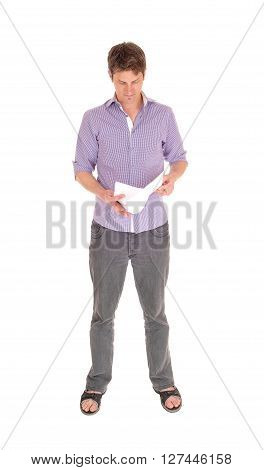 A young man in jeans and a purple shirt standing relaxed isolated for white background and reading in his papers.