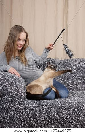 young woman playing with air prey teaser cat toy