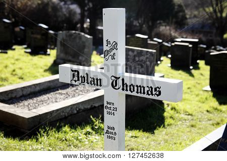 Laugharne,Wales, UK, February 24, 2016 : The grave of Dylan Thomas is marked by just a simple plain tombstone white cross in St Martin's Church overspill cemetery
