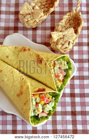 Pita bread stuffed with corn, eggs, crab meat, leaf lettuce. Salad in pita bread on a white plate