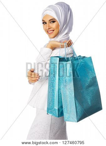 Muslim woman in white dress with bags isolated