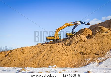 Yellow excavator at work in winter outdoors