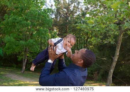 A father holding his baby while outside in a park