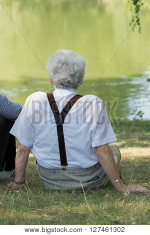 Retiree sitting on the grass at the lake