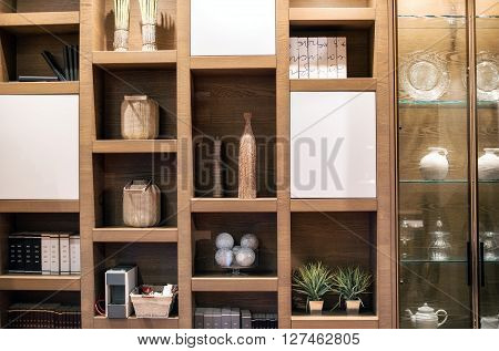 Wooden interior wall unit with separate compartments ornaments and a glass showcase in an interior decor and furnishing background