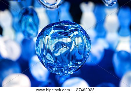 Cool abstract blue glass ball with creases floating above other translucent objects