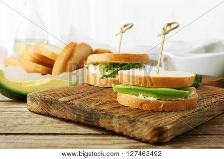 Vegetarian avocado sandwiches on a wooden board