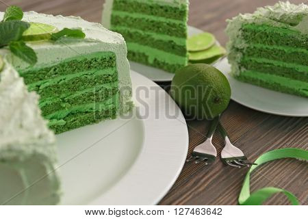 Piece of delicious creamy lime cake on wooden table closeup