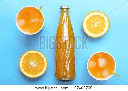 Orange drink with ice cubes on blue background