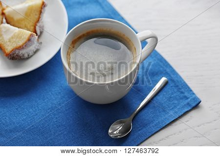 Cup of coffee with cake on a blue napkin