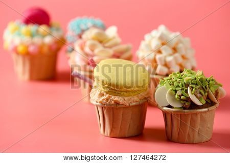 Tasty cupcakes with original decoration on pink background
