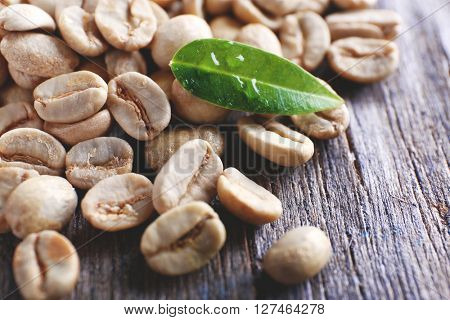 Green coffee beans with a leaf on  wooden table