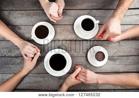Friends drinking coffee and holding hands on wooden table