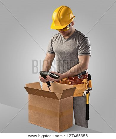 construction worker unpacks the box with delivery drill on gray background