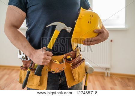 construction worker with tool belt, helmet and hammer
