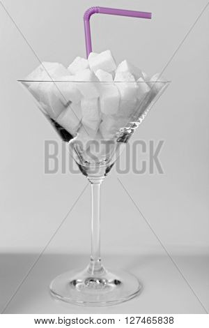 Martini glass with lump sugar and cocktail straw on grey background