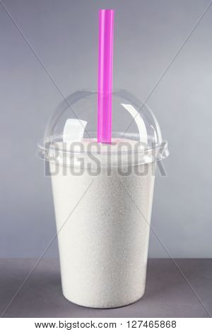 Plastic glass full of sugar with straw on grey background
