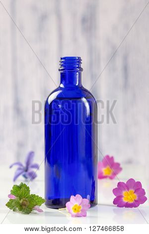 Blue bottle of essential oil with fresh flowers